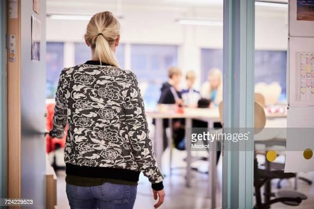 Rear view of mid adult teacher entering in classroom