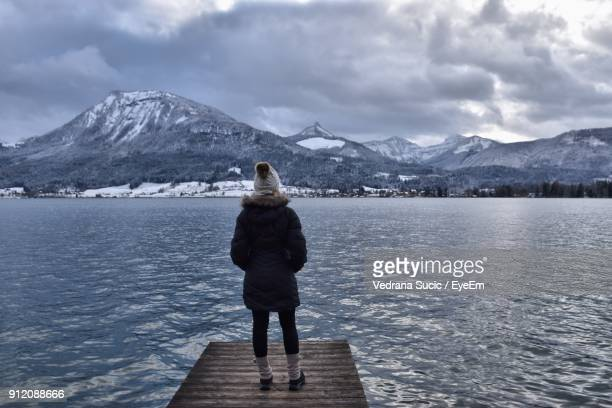 Rear View Of Mid Adult Woman In Warm Clothing Standing On Pier Over Lake Against Cloudy Sky