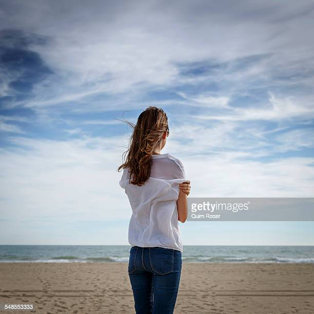 Rear view of mid adult woman looking out to sea, Castelldefels, Catalonia, Spain