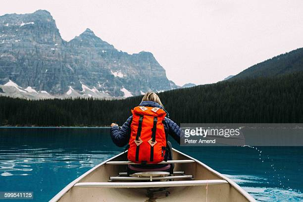 Rear view of mid adult woman paddling canoe, Moraine lake, Banff National Park, Alberta Canada