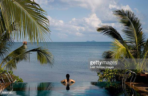 rear view of mid adult woman relaxing in infinity pool, koh samui, thailand - infinity pool foto e immagini stock