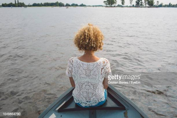 Rear View Of Mid Adult Woman Sitting In Boat On Lake