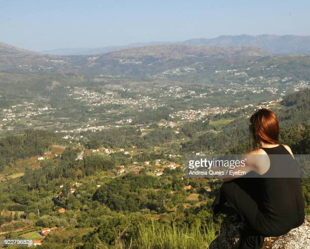 Rear View Of Mid Adult Woman Sitting On Mountain Against Sky