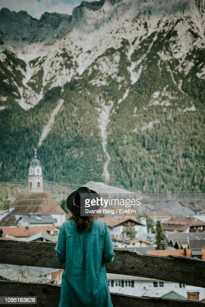 rear view of mid adult woman standing against snowcapped mountain - mittenwald stock-fotos und bilder