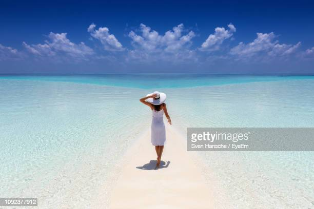 rear view of mid adult woman standing at beach against blue sky during sunny day - maldives stock pictures, royalty-free photos & images