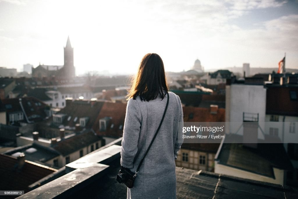 Rear View Of Mid Adult Woman Standing By Cityscape Against Sky : Stock-Foto