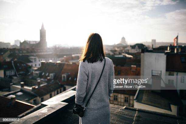 rear view of mid adult woman standing by cityscape against sky - eine person stock-fotos und bilder