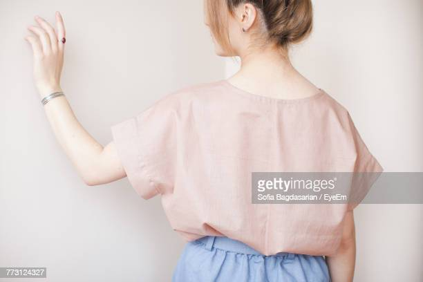 Rear View Of Mid Adult Woman Standing By White Walls