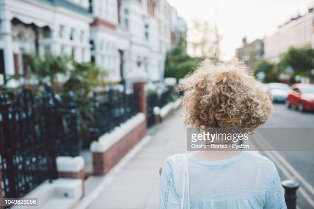 Rear View Of Mid Adult Woman Standing On Footpath In City