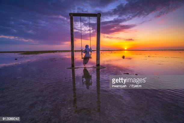 rear view of mid adult woman swinging at beach against sky during sunset - lombok fotografías e imágenes de stock