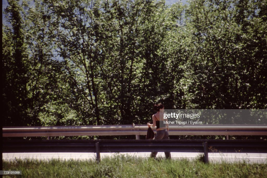 Rear View Of Mid Adult Woman Walking On Road By Trees : Photo