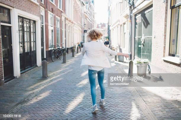 rear view of mid adult woman walking on street in city - bortes stockfoto's en -beelden