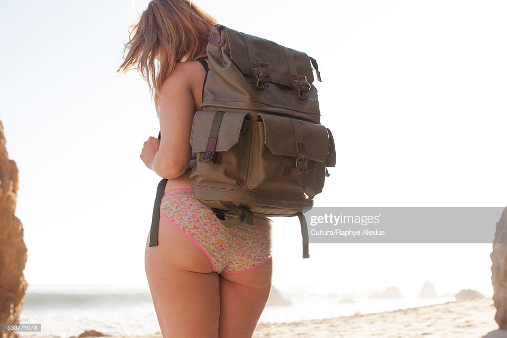 Rear view of mid adult woman wearing backpack and lace knickers on El Matador Beach, Malibu, California, USA : Foto stock
