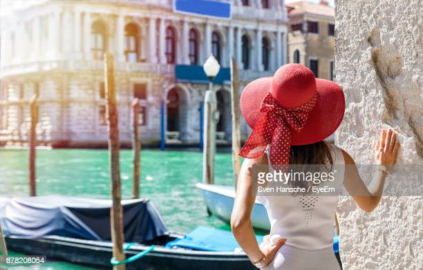 Rear View Of Mid Adult Woman Wearing Hat Standing By River In City