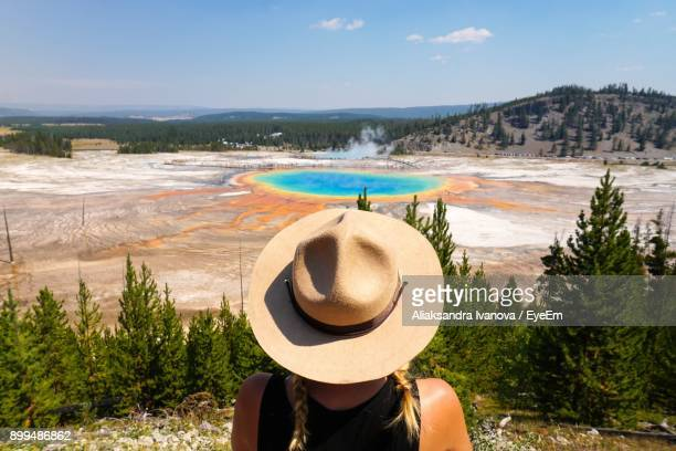 rear view of mid adult woman wearing hat standing on field against sky - yellowstone national park stock pictures, royalty-free photos & images