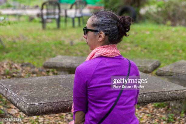 rear view of mid adult woman wearing sunglasses sitting at park - florin seitan stock pictures, royalty-free photos & images