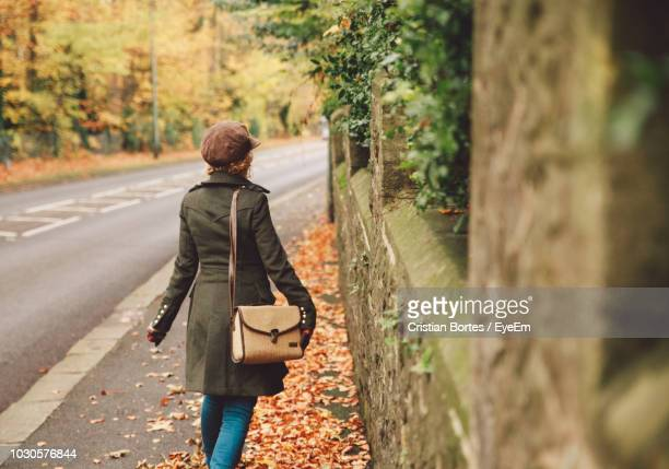 Rear View Of Mid Adult Woman Wearing Winter Coat While Walking On Road