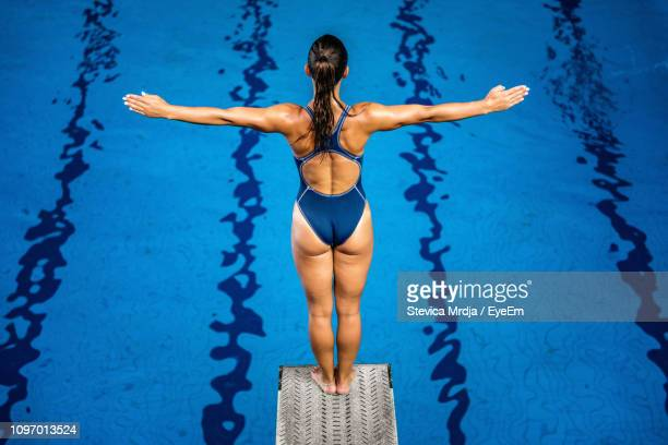 rear view of mid adult woman with arms outstretched standing on diving platform - diving platform stock pictures, royalty-free photos & images