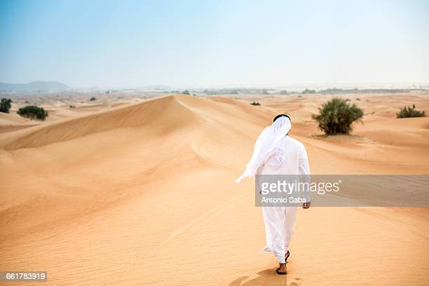 Rear view of middle eastern man wearing traditional clothes walking in desert, Dubai, United Arab Emirates