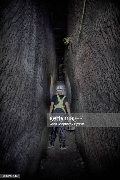 Rear View Of Miner Holding Work Tool While Working In Underground Tunnel