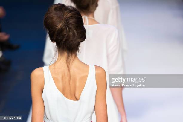 rear view of models walking on ramp walk - fashion week stock pictures, royalty-free photos & images