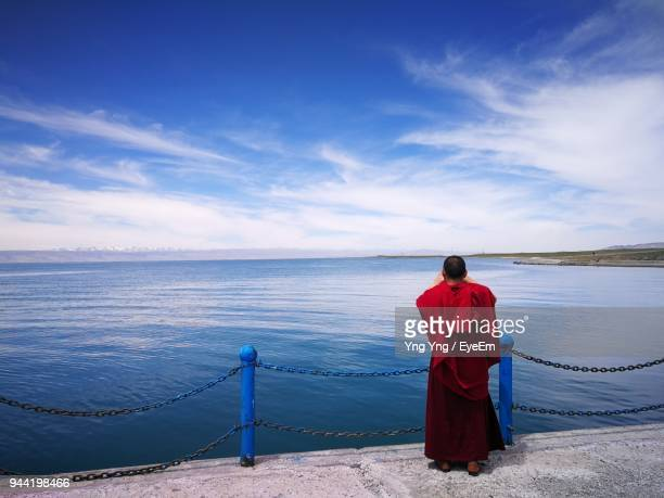 rear view of monk standing on pier by sea against sky - ceremonial robe stock pictures, royalty-free photos & images