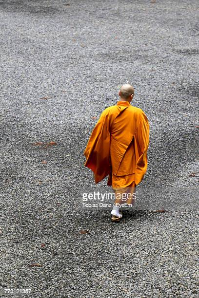 Rear View Of Monk Walking On Street