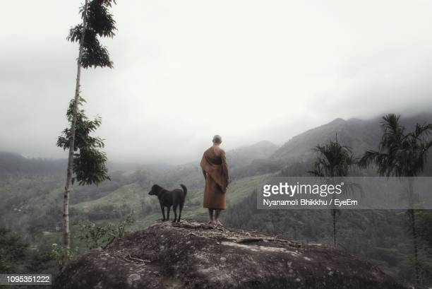 rear view of monk with dog standing on mountain peak against clear sky - religious occupation stock pictures, royalty-free photos & images