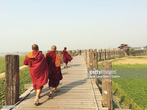 rear view of monks walking on boardwalk against clear sky - ceremonial robe stock pictures, royalty-free photos & images