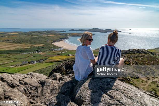 rear view of mother and daughter chatting on a mountain top (carn llidi) overlooking whitesands bay, pembrokeshire - natural parkland stock pictures, royalty-free photos & images