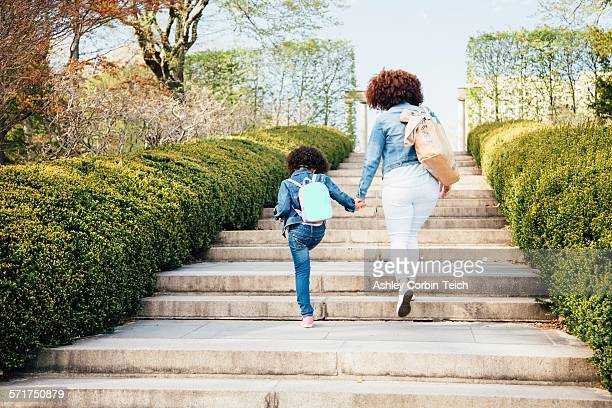 Rear view of mother and daughter holding hands going up stairway