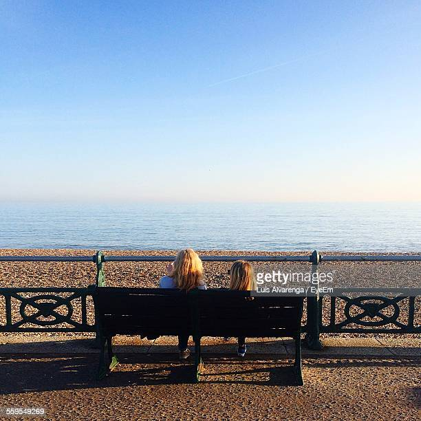 rear view of mother and daughter looking at sea view against clear blue sky - luis alvarenga - fotografias e filmes do acervo
