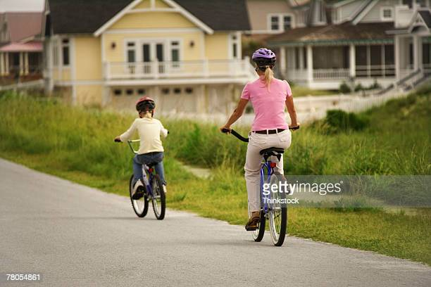 rear view of mother and daughter riding bikes together - thinkstock foto e immagini stock