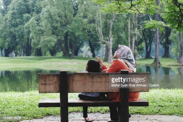 rear view of mother and daughter sitting on bench in park - single mother stock pictures, royalty-free photos & images