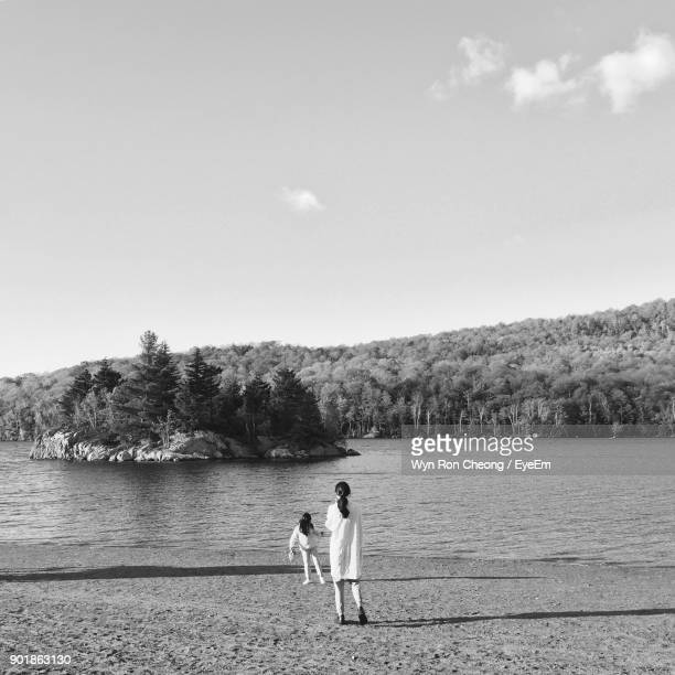 rear view of mother and daughter standing against lake - amour noir et blanc photos et images de collection