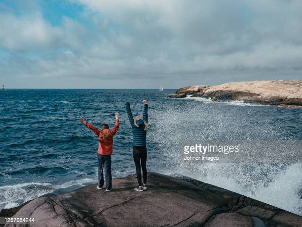 rear view of mother and daughter  standing at sea - nature reserve foto e immagini stock