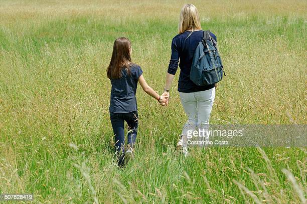 Rear view of mother and daughter strolling through long grass field