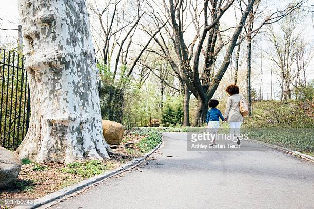 Rear view of mother and daughter walking along pathway holding hands