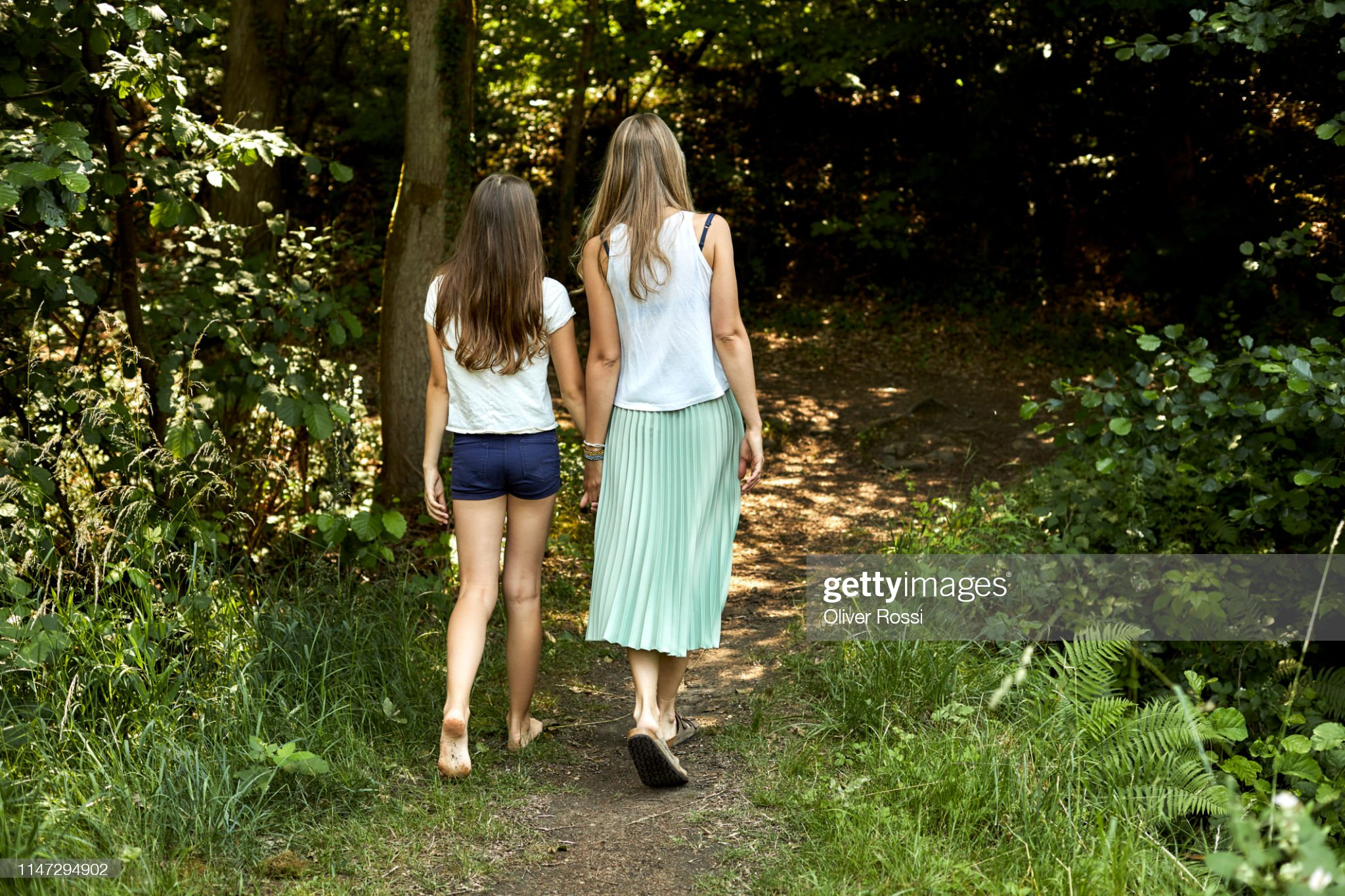 https://media.gettyimages.com/photos/rear-view-of-mother-and-daughter-walking-hand-in-hand-on-a-forest-picture-id1147294902?s=2048x2048