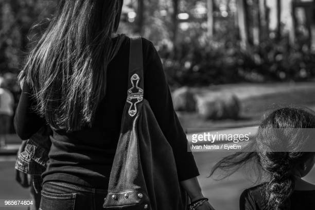 Rear View Of Mother And Daughter Walking On Road