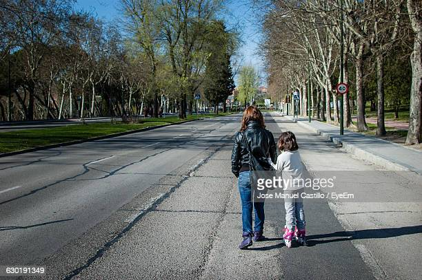 Rear View Of Mother And Daughter Walking On Street Amidst Trees