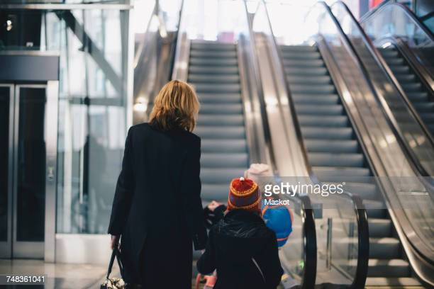Rear view of mother and daughters walking towards escalator at railroad station