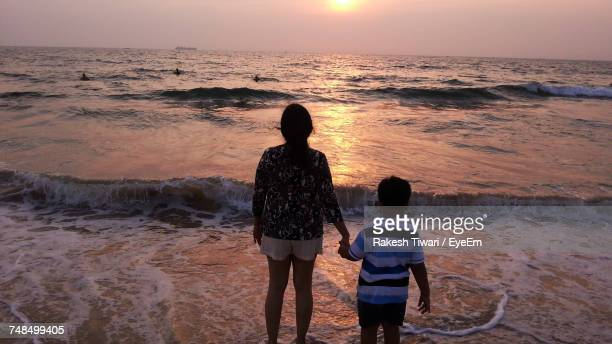 Rear View Of Mother And Son Holding Hands While Standing On Shore During Sunset