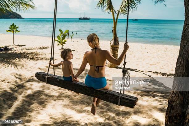 rückansicht des mutter und sohn hand in hand beim schwingen am strand. - thailand stock-fotos und bilder