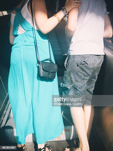Rear View Of Mother And Son On Escalator