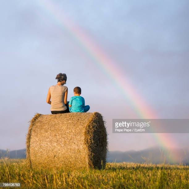 Rear View Of Mother And Son Sitting On Hay Bale Against Sky During Sunset