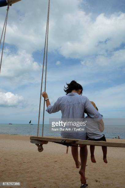 Rear View Of Mother And Son Sitting On Swing At Beach
