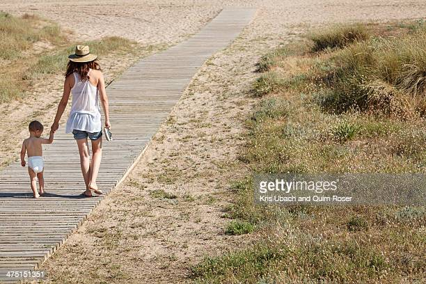 Rear view of mother and son walking down boardwalk to beach