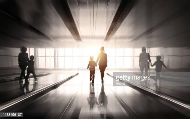 achteraanzicht van moeder en zoon lopen in het licht - onherkenbaar persoon stockfoto's en -beelden
