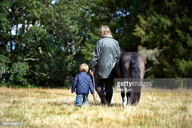 Rear view of mother and son walking pony in field